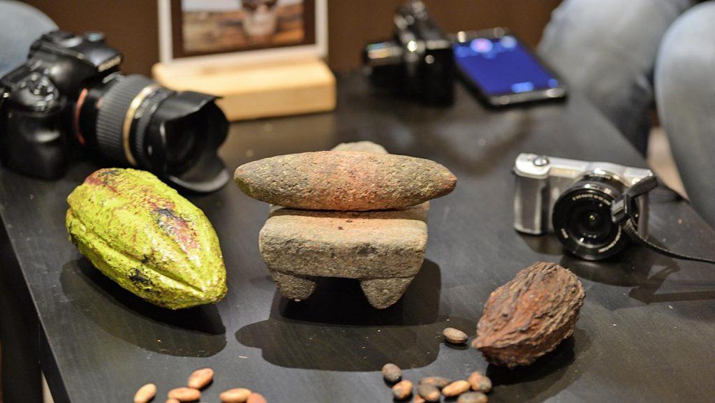 Die Arbeitsutensilien der Bloggerreise mit Arosa und ein paar Kakaobohnen. Foto: André Lenthe