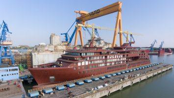 Der etwa 6.500 Tonnen schwere Schiffsrumpf wurde auf dem Gelände der VARD Werft in Tulcea in Rumänien in einem dreistündigen Absenkprozess über eine Hebebühne zu Wasser gelassen. Foto: Hapag-Lloyd Cruises / Bogdan Vasilescu