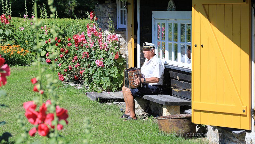 Mann mit Akkordeon im Garten, Saaremaa, Estland / Foto: Oliver Asmussen/oceanliner-pictures.com